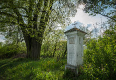 Roadside chapel under the linden tree Stock Photo