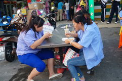 Roadside food stalls, the workers are eating snacks Royalty Free Stock Image