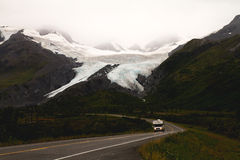 Roadside Glacier on Cloudy Day. A campervan drives past an incredible roadside Glacier in Alaska Stock Photography