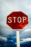 Roadside red stop sign on a cloudy background. Royalty Free Stock Photos