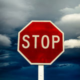 Roadside red stop sign on a cloudy background. Royalty Free Stock Images