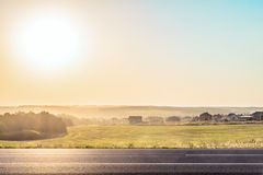 Roadside rural landscape in light of the low evening sun backlight Stock Photos
