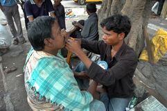 Roadside saloon. A man is making his shave in a roadside saloon at slum area in India Royalty Free Stock Photos