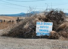 Roadside sign in the tumbleweeds stock photography