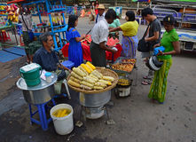 Roadside vendors selling sweet corn, cut red watermelon and vegetarian fritter Royalty Free Stock Photography