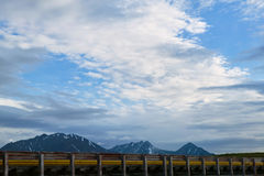 Roadside view of distant Alaskan mountains. A roadside view of distant snow capped Alaskan mountains and foreground kerb railing Royalty Free Stock Photo