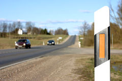 Roadside warning. Post, rural scene, country road and 2 cars royalty free stock photos