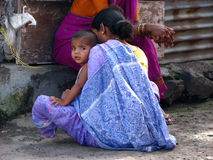 Roadside Woman. A poor Indian woman with her child sitting on the roadside Stock Photos