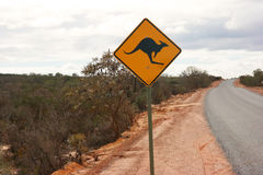 Roadsign de kangourou à côté de route australienne photos stock