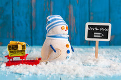 Roadsign showing the way to The north pole and. A roadsign showing the way to the north pole and Snowman with red sled And gift or present stand near word North Royalty Free Stock Images