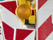 Roadsigns battered. Old and scratched, red-and-white striped Strassenabsperrschilder with orange flashing light stock images