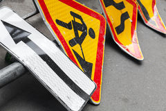 Roadsigns lay on asphalt road. Under construction. Bright red and yellow roadsigns lay on the asphalt road. Under construction and narrowing of the road marking royalty free stock photos