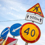 Roadsigns over cloudy blue sky. Men at work Royalty Free Stock Image