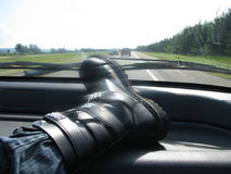 Roadtrip!. Boots over the dashboard during a roadtrip in an old rusty van Royalty Free Stock Photo