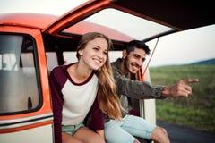 Μια νεολαία συνδέει σε ένα roadtrip μέσω της επαρχίας, καθμένος σε minivan στοκ εικόνες