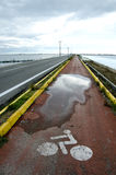 Roadway across lake. A view of a roadway or causeway with a bicycle lane across a lake Stock Photos