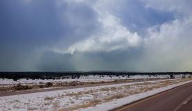 The roadway is clear and the snow covers the landscape side road just a snowfall in New Mexico. The roadway is clear and the snow storm clouds covers the royalty free stock photos