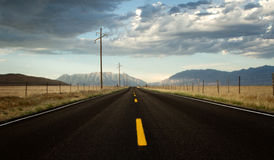 A roadway in a countryside with mountains. A roadway in a countryside landscape with mountains at sunset Stock Image