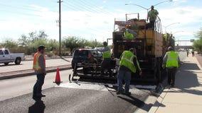 Roadway workers resurfacing street. stock video