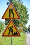 Roadwork dos sinais de estrada, redução da estrada no direito contra uma estrada Foto de Stock Royalty Free