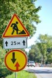 Roadwork dos sinais de estrada, vantagem antes de tráfego próximo contra uma estrada Foto de Stock Royalty Free