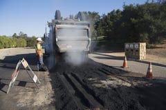 Roadworker repaves el camino con el vapor, impulsión de Encino, opinión del roble, California, los E.E.U.U. Imágenes de archivo libres de regalías