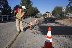 Roadworker repaves a estrada com vapor, movimentação de Encino, opinião do carvalho, Califórnia, EUA Fotos de Stock