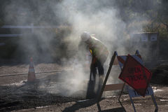 Roadworker repaves road with steam, Encino Drive, Oak View, California, USA Stock Photo