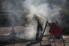 Roadworker repaves road with steam, Encino Drive, Oak View, California, USA Stock Photo