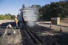 Roadworker repaves road with steam, Encino Drive, Oak View, California, USA Royalty Free Stock Images
