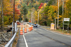 Roadworks along a Road Lined with Colourful Autumnal Trees. Roadworks along a Mountain Road in Autumn. White and Orange Traffic Cones Line the Construction Area Stock Photography