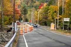 Roadworks längs en väg som fodras med färgglade höstliga träd Arkivbild