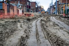 Roadworks on muddy street. View of street with roadworks and excavations on dirty mud Stock Photos