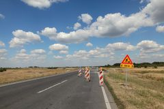 Highway or road in reconstruction. Roadworks, road signs at a highway or road on reconstruction with blue sky and clouds Royalty Free Stock Photography