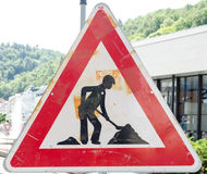 Roadworks. A rusty triangular sign warning of roadworks ahead with a modern city building in the background Royalty Free Stock Photo