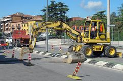 Roadworks with a scraper to work in the middle of the road Royalty Free Stock Photography