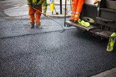 A roadworks on the street new asphalt with worker. S, Road Roller Road Construction Machinery Royalty Free Stock Images