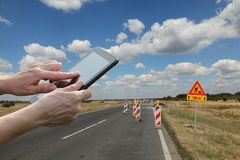 Worker inspecting highway or road in reconstruction. Roadworks, workers hands using tablet with road signs and road on reconstruction in backround Stock Image