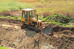 Roadworks, yellow bulldozer work. Roadworks, yellow bulldozer in the sunny day Royalty Free Stock Photography