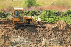 Roadworks, yellow bulldozer work. Roadworks, yellow bulldozer in the sunny day Stock Photography