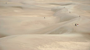 Roam the endless desert. Different people in the emptiness of a sand desert Stock Photo