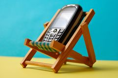 Roaming - stay in touch. Conceptual photo, cellphone on a deckchair - stay connected during your holidays Royalty Free Stock Photos