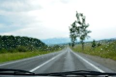 On the road in a rainy day. Green mountain road in a rainy day seen by inside the car Stock Images