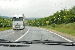 On the road in a rainy day. Seen by inside the car Stock Images