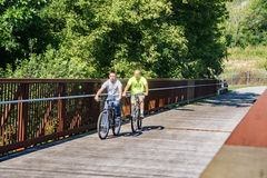 Two Cyclists without Protective Helmets. Roanoke County, VA – August 19th: A pair of cyclist enjoy a ride on the Roanoke River Greenway without protective Stock Image