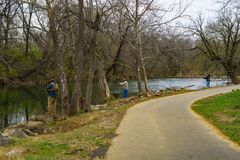 Three Fishermen Fishing for Rainbow Trout. Roanoke County, Virginia USA – March 18th: A three fishermen fishing for rainbow trout in the beautiful Roanoke stock photos