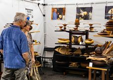 Woodturner at the 60th Annual Sidewalk Art Show – Roanoke, VA. Roanoke, VA – June 2nd: Couple enjoy the work of a local woodturner at the 60th royalty free stock image