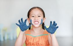 Roar little Asian girl with her blue hands in the paint in children room. Focus at baby hands.  royalty free stock photography