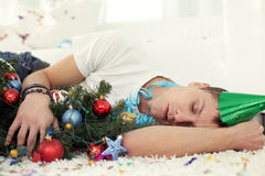 Roaring Christmas. Young drunken man sleeping on floor with Christmas tree and in party hat Stock Photography