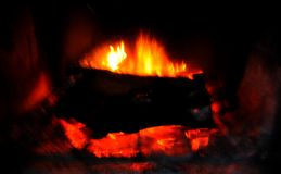 Roaring Fire Flames in Fireplace. A roaring fire flares to life in a fireplace on a cold winter evening in the San Diego mountains of California royalty free stock images